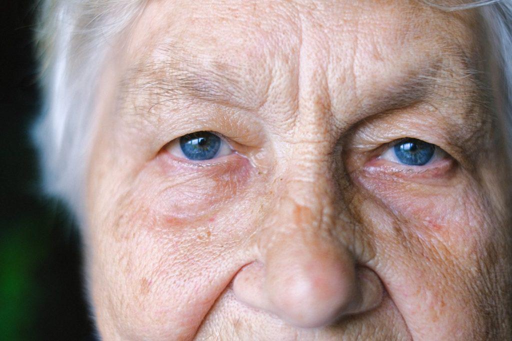 crop elderly woman with blue eyes